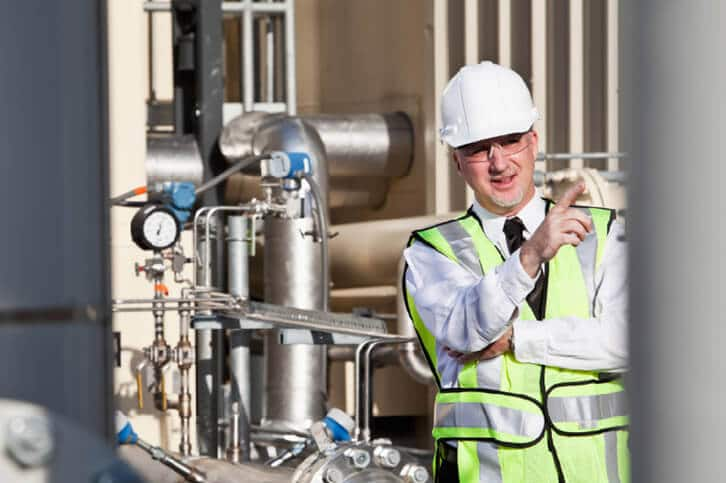 A process engineer standing outside in front of a piping installation.