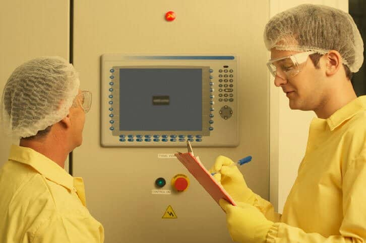 A process technician standing in front of a monitoring screen talking to his colleague.