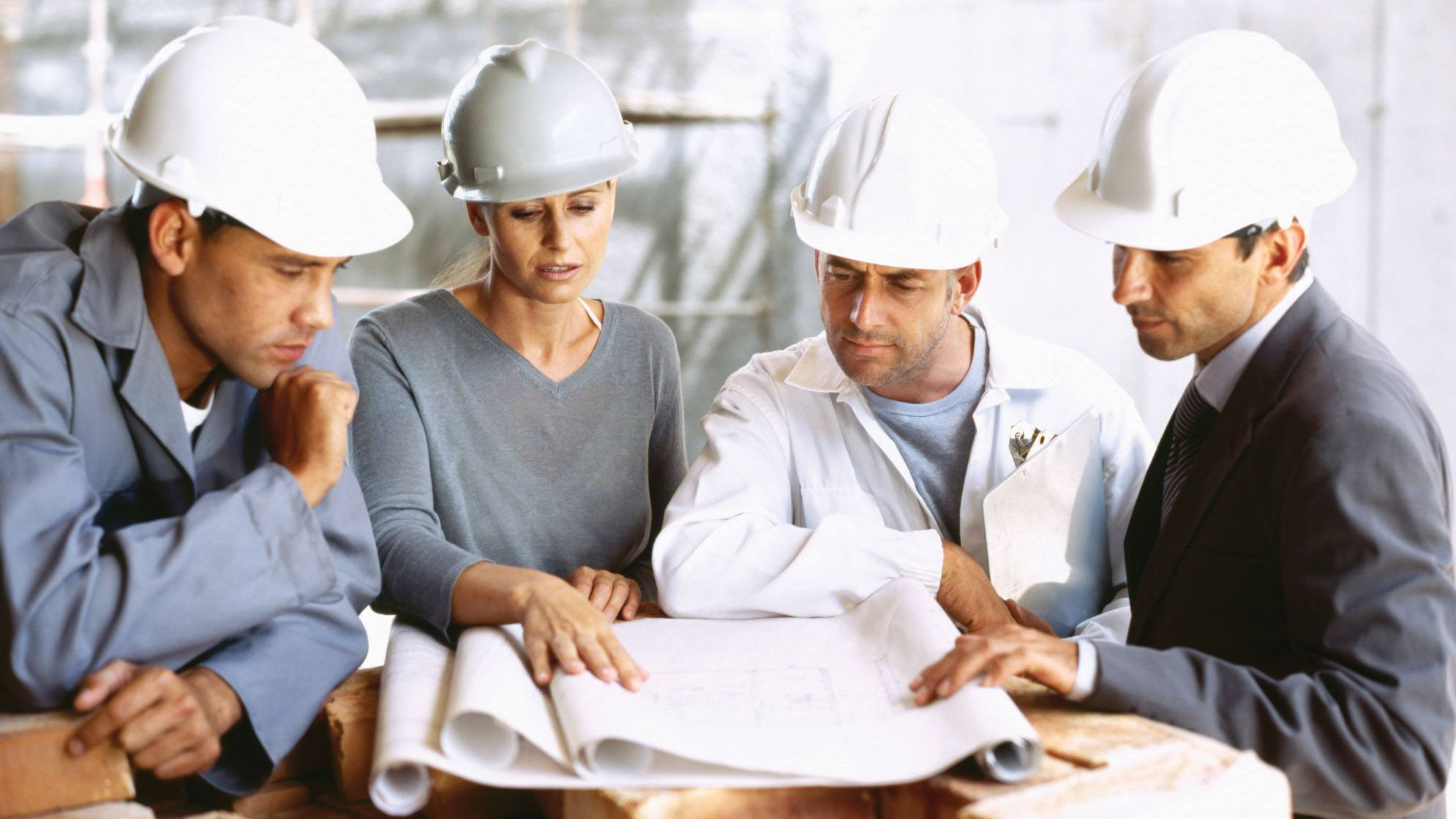 project engineer in a meeting with other project engineers standing around reading a piping and instrument diagram.
