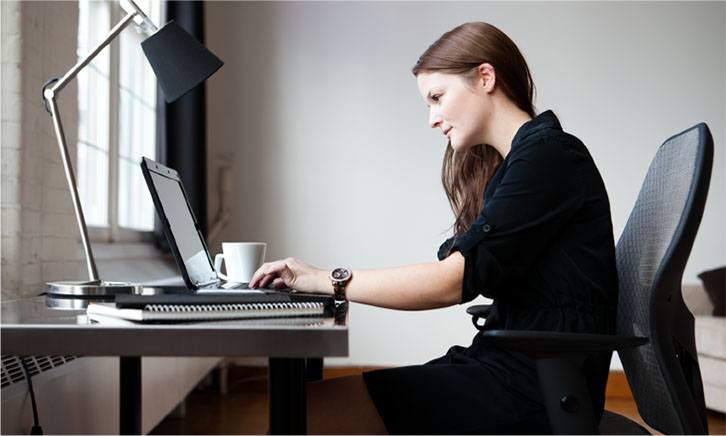 photo-of-woman-sat-at-desk-using-laptop-suggesting-student-of-an-online-course