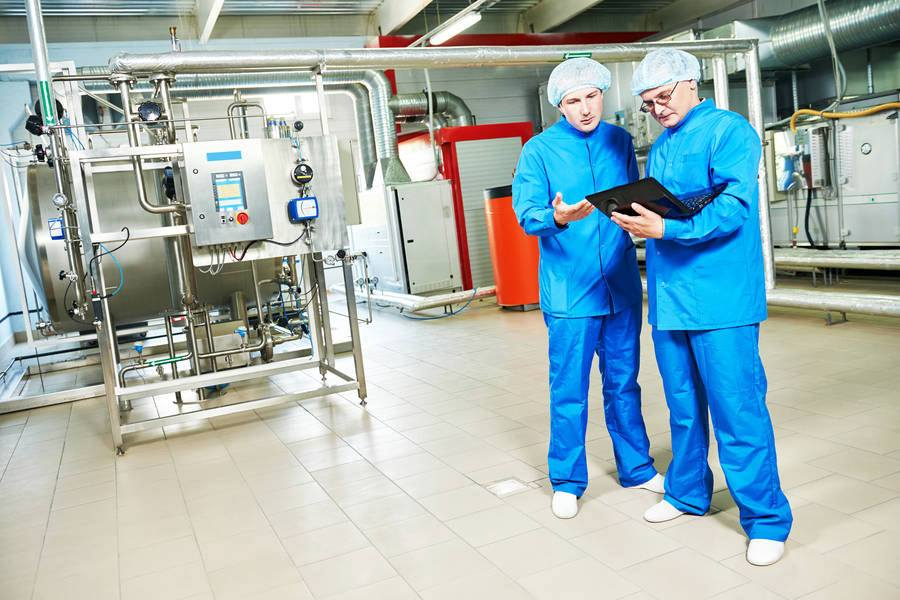 production-supervisor-and-staff-member-in-personal-protective-equipment-in-pharmaceutical-manufacturing-facility