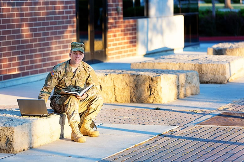 man-in-military-uniform-sitting-outside-using-laptop-to-demonstrate-how-online-learning-works
