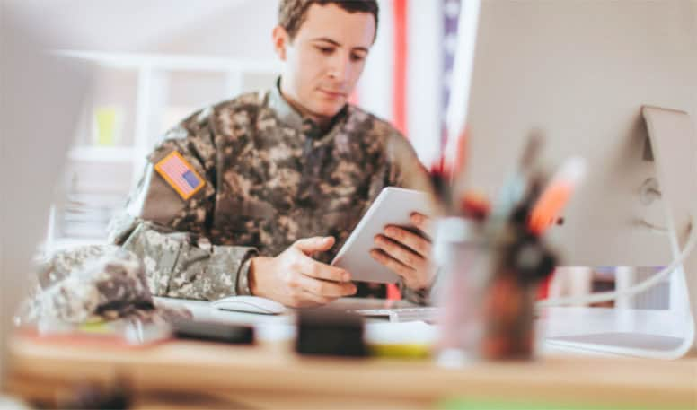 man-in-military-uniform-sitting-at-desk-using-tablet-to-demonstrate-how-the-course-works
