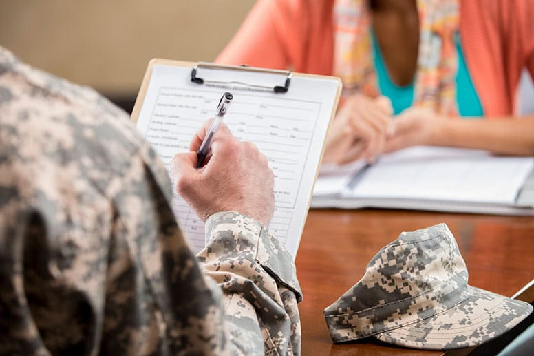 person-in-military-uniform-sitting-at-desk-with-clipboard-as-if-applying-for-scholarship