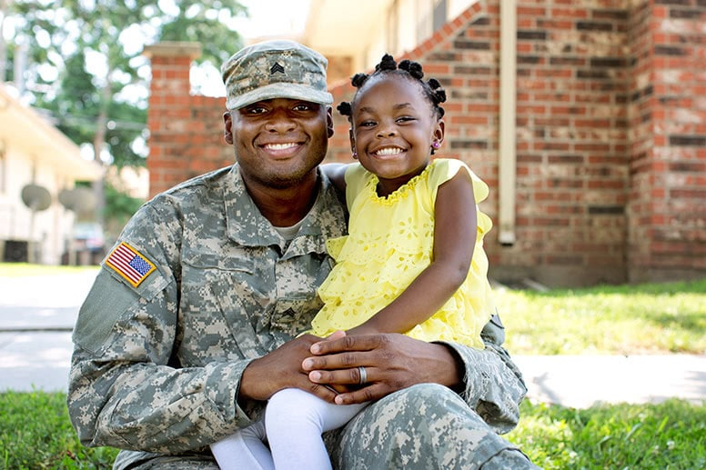 veteran-in-uniform-and-young-girl-smiling-at-camera