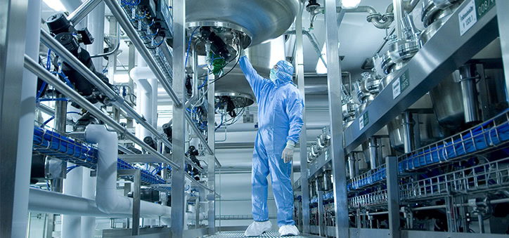 man in protective clothing operating manufacturing equipment
