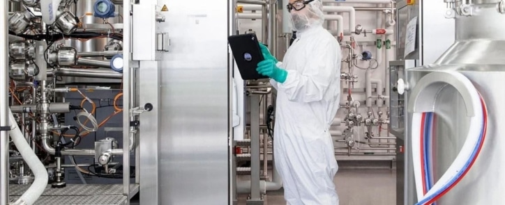man with machinery looking at tablet